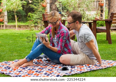 Romantic couple sitting on a blanket with tablet pc at summer green park. They are happy - stock photo