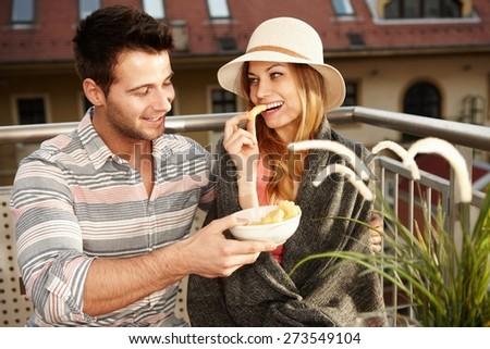 Romantic couple sitting on balcony, eating, smiling, hugging. - stock photo