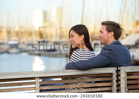 Romantic couple sitting on bench in old harbour, Port Vell, Barcelona, Catalonia, Spain. Happy woman and man embracing enjoying life and romance outside. Multiracial Caucasian Asian couple in love. - stock photo