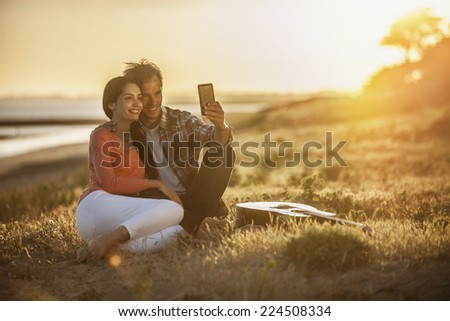 Romantic couple sitting on the beach at sunset and taking a selfie - stock photo