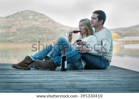 Romantic Couple sitting on the pier with red wine. - stock photo