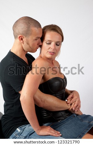 Romantic couple sitting together, he has his hand on her thigh and she is holding his chest and leaning forward for a kiss