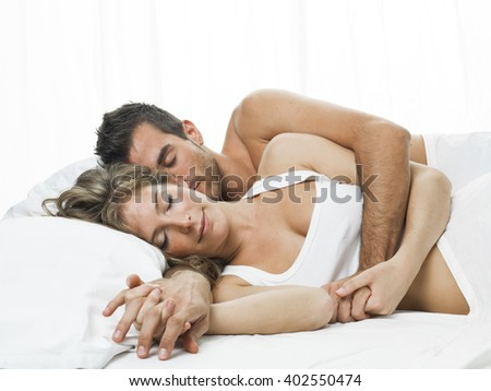 romantic couple sleeping in a white bed