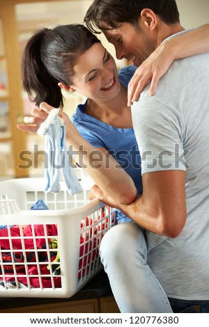 Romantic Couple Sorting Laundry In Kitchen - stock photo