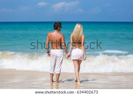 Romantic couple stand on the beach and enjoying beautiful sea view, side view, spending time together, summer vacation concept