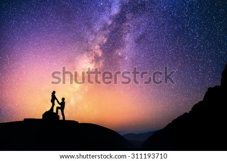 Romantic couple standing together holding hands in the mountains. Beautiful Milky Way galaxy on the background. - stock photo