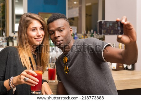 Romantic couple taking self portrait with mobile phone in a bar. - stock photo