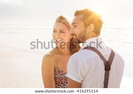 Romantic couple together at beach. Carefree couple on the beach in casual clothing at sunset. Young couple looking away.