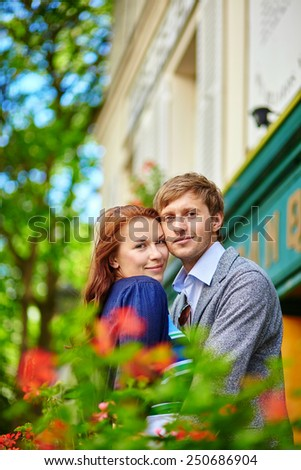 Romantic couple together on balcony of a house or hotel with blossoming geranium - stock photo