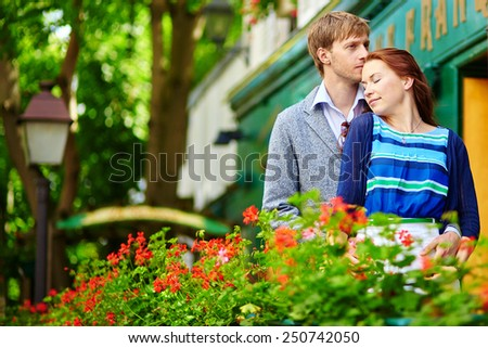 Romantic couple together on balcony of a house or hotel with blossoming geranium