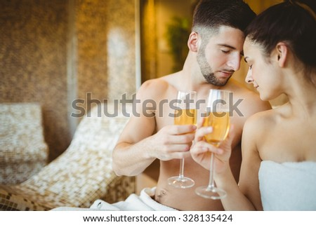 Romantic couple together with champagne glasses at the spa