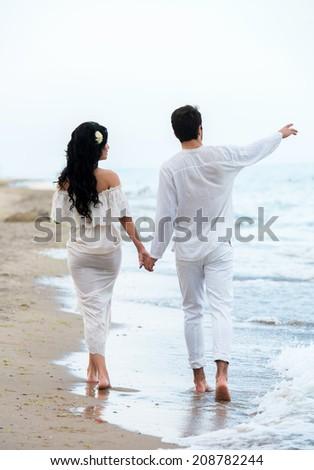Romantic couple walking along the seaside - stock photo