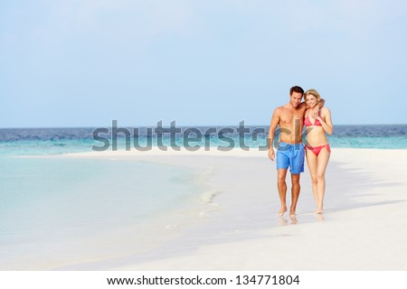 Romantic Couple Walking On Beautiful Tropical Beach - stock photo