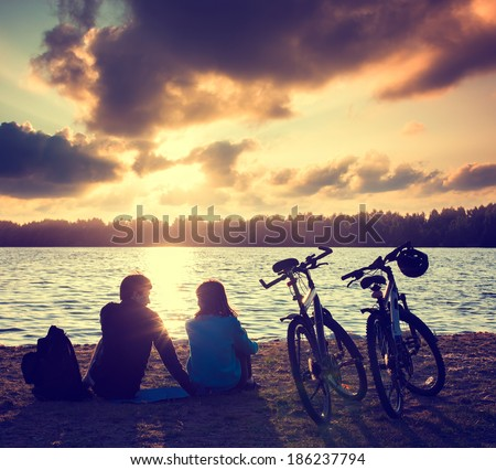 Romantic Couple with Bicycles Relaxing at Sunset. Summer Nature Background. Active Leisure Concept. Toned Photo. - stock photo