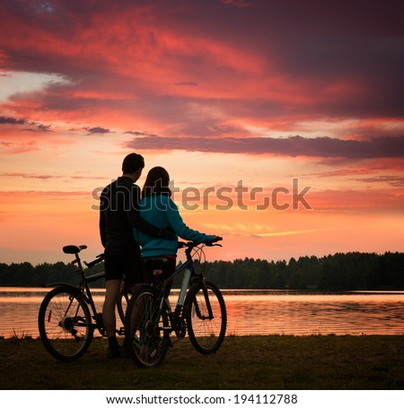 Romantic Couple with Bicycles Watching Sunset. Summer Nature Background with Beautiful Clouds, Sky and River. Active Leisure Concept. - stock photo