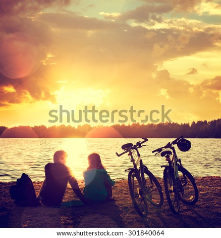 Romantic Couple with Bikes Relaxing at Sunset by the Lake. Fall in Love Concept. Toned Photo with Bokeh. - stock photo