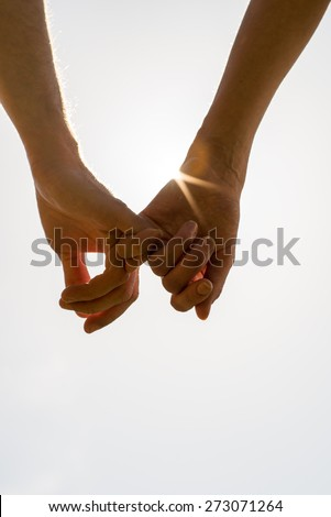 Romantic couple with clasped hands backlit by a bright morning sunburst in a closeup conceptual image of love and friendship. - stock photo
