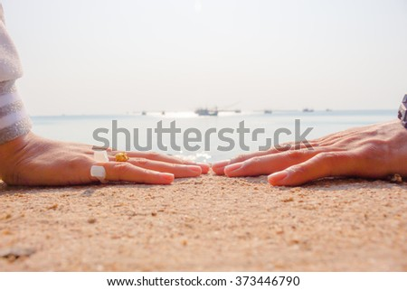 Romantic couple with clasped hands In the atmosphere of the sea by a bright evening sun in a closeup conceptual image of love, commitment and friendship. - stock photo