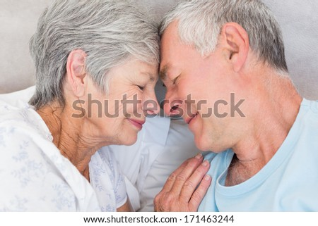 Romantic couple with head to head lying in bed - stock photo
