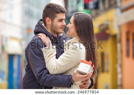 Romantic couple. Young man holding gift for his girlfriend - stock photo