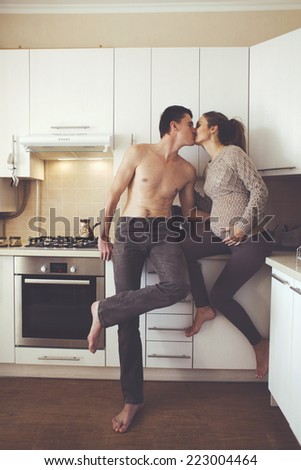 Romantic cozy home portrait of beautiful loving couple making coffee together at the kitchen at home