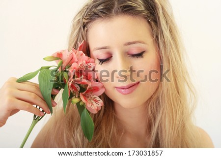 Romantic cute woman with pink flowers portrait in natural warm colors