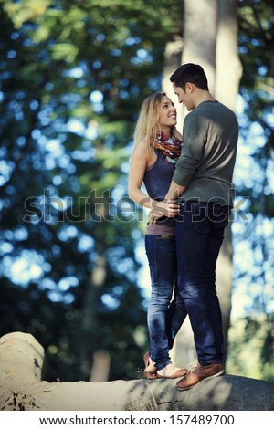 romantic date in the forest - young couple standing on a tree trunk smiling at each other - stock photo