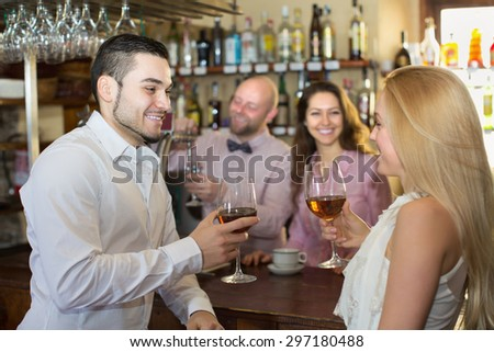 Romantic date of cheerful couple drinking wine at bar and smiling
