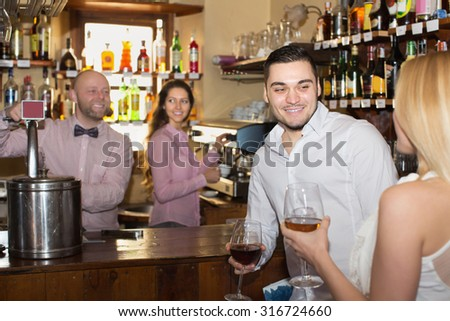 Romantic date of positive couple drinking wine at bar and smiling - stock photo