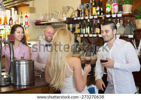 Romantic date of young positive couple drinking wine at bar and smiling - stock photo