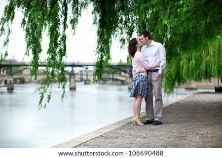 Romantic dating couple is kissing under the willow - stock photo