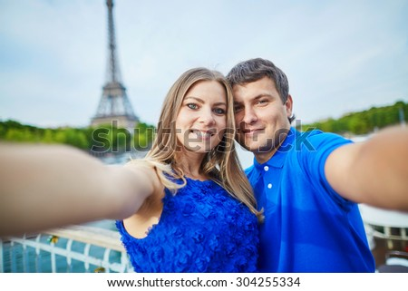 Romantic dating couple on a bridge over the Seine in Paris, taking funny selfie, Eiffel tower is in the background
