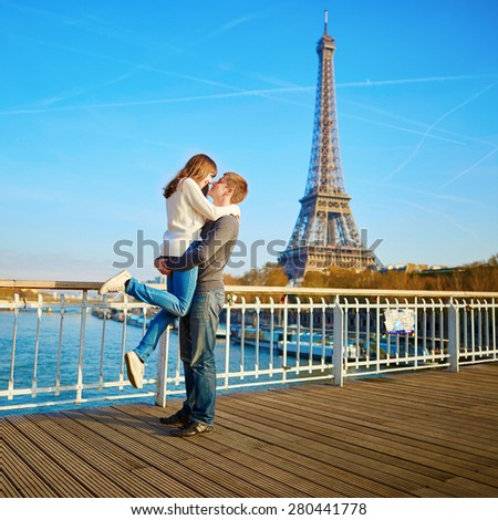 Romantic dating loving couple spending time together in Paris near the Eiffel tower - stock photo