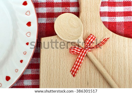 Romantic dinner: Kitchen board and wooden spoon with bow