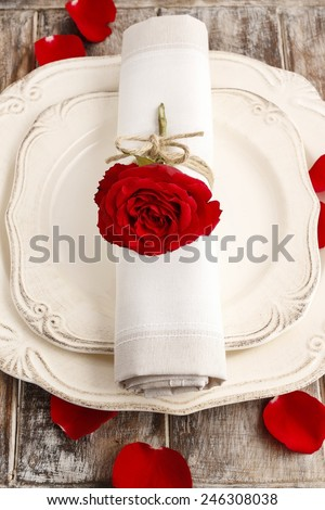 Romantic dinner: napkin ring made with red rose, petals around the plate - stock photo
