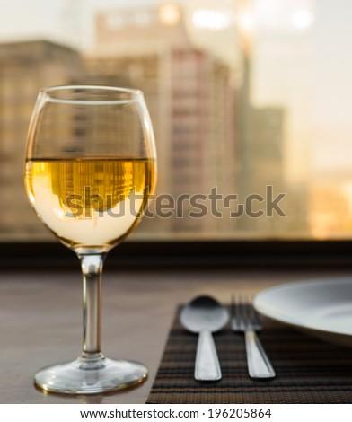 Romantic dinner setting. Glass of white wine in the restaurant. - stock photo