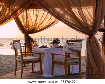Romantic dinner setting on the beach - stock photo