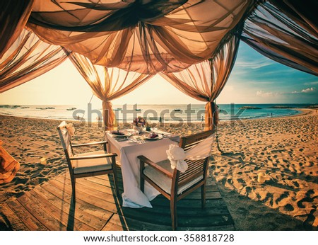 Romantic dinner setting on the beach at sunset - stock photo