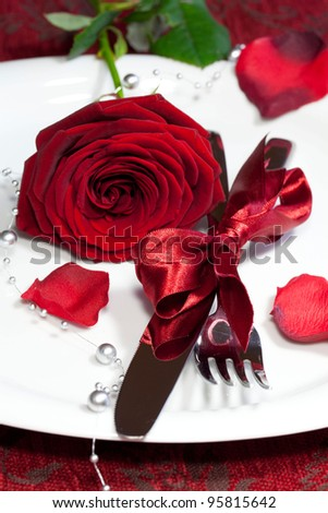 Romantic dinner setting with a rose - stock photo