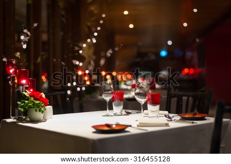 romantic dinner setup, red decoration with candle light in a restaurant. Selective focus. - stock photo