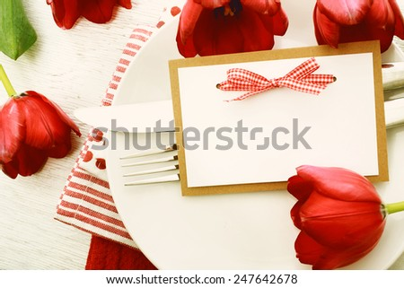 Romantic dinner table setting with blank note card and red tulips - stock photo