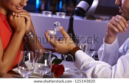 Romantic dinner with engagement ring. Young man proposing to woman. - stock photo