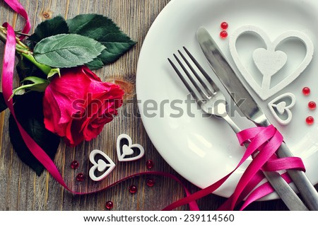 Romantic dinner with rose, tableware and hearts on wooden background - stock photo
