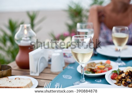 Romantic dinner with white wine. In the background a girl is out of focus. - stock photo