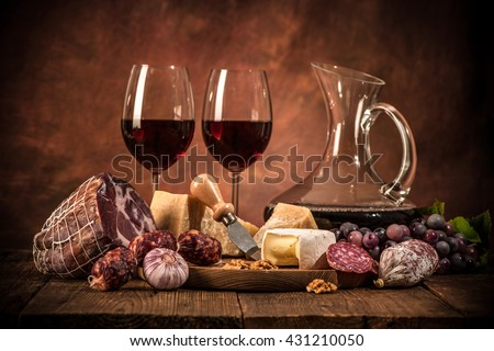Romantic dinner with wine, cheese and traditional sausages - stock photo