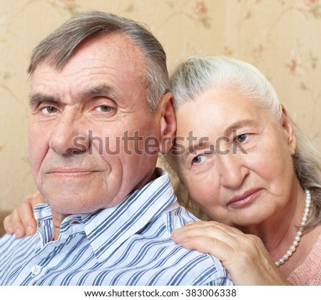Romantic elderly man and woman sitting close together on sofa in their living room in a loving embrace  looking at camera - stock photo