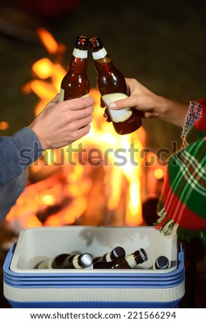 Romantic evening. Couple campfire while camping drinking beer - stock photo