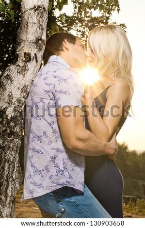 romantic evening date on nature, couple  embrace on beautiful sunset - stock photo