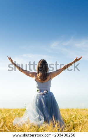 romantic fairy person: image of beautiful carefree blond young lady having fun wearing long blue ball dress with arms wide expand looking up on wheat field and blue sky background copyspace - stock photo