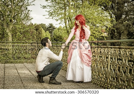 Romantic Fairy Tale Couple in Beautiful Palace Garden in Peaceful Idyllic Setting, Man is Proposing to Woman, Prince and Princess Gazing at Each Other - stock photo